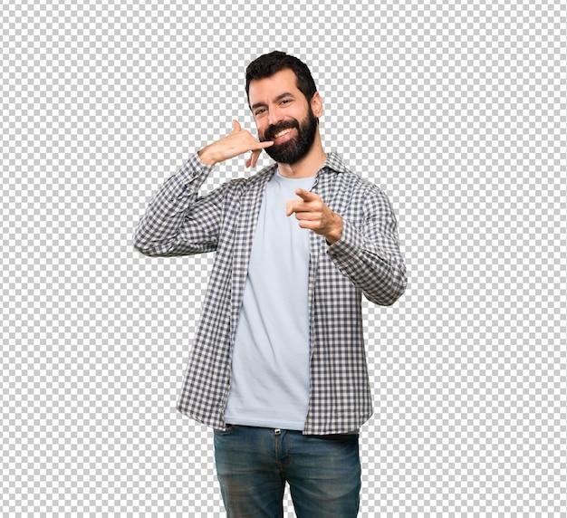 Uomo bello con la barba che fa gesto del telefono e che indica fronte
