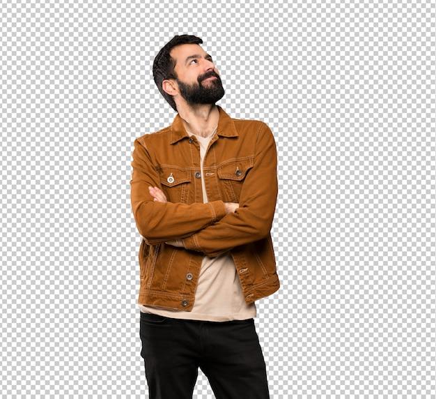 Uomo bello con la barba che osserva in su mentre sorridendo