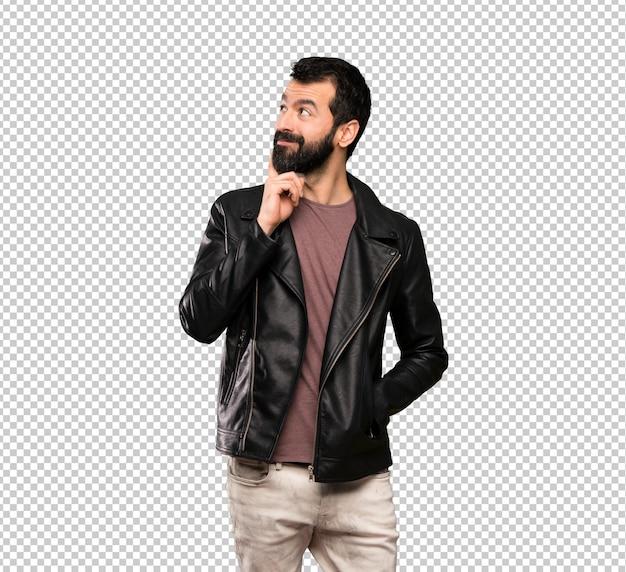 Uomo bello con la barba che pensa un'idea mentre osserva in su