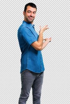 Uomo bello con la camicia blu che presenta e che invita a venire