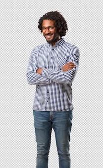 Uomo bello dell'afroamericano di affari che attraversa le sue braccia, sorridenti e felici, essendo sicuro ed amichevole