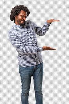 Uomo bello dell'afroamericano di affari che tiene qualcosa con le mani, mostrando un prodotto, sorridente e allegro, offrendo un oggetto immaginario