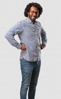 Uomo bello dell'afroamericano di affari con le mani sui fianchi, in piedi, rilassato e sorridente, molto positivo e allegro
