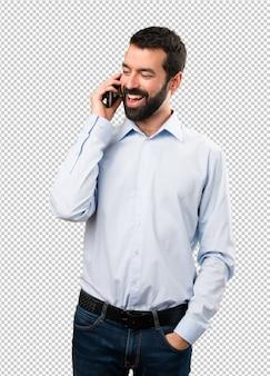 Uomo bello felice con la barba che comunica con mobile