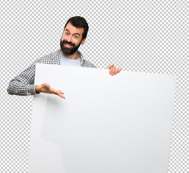 Uomo bello felice con la barba che tiene un cartello vuoto