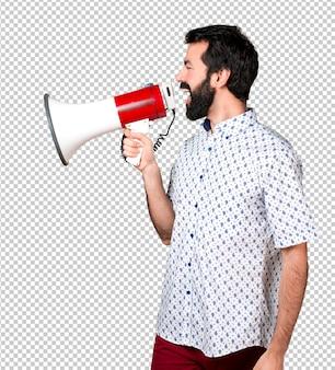 Uomo castana bello con la barba che grida dal megafono