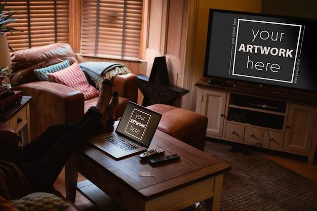 Uomo che per mezzo del computer portatile e guardando la tv