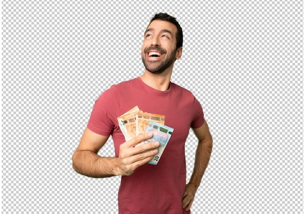 Uomo che prende un sacco di soldi in posa con le braccia all'anca e ridendo