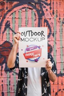 Uomo che presenta il mockup di poster davanti al muro di graffiti