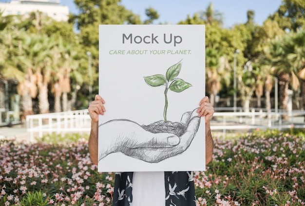 Uomo che presenta il mockup di poster di fronte al parco