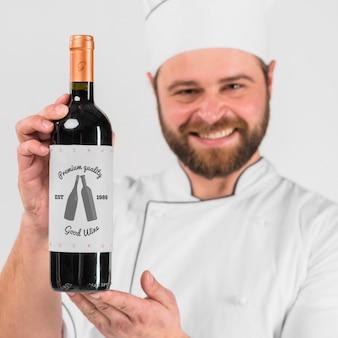 Uomo che presenta la bottiglia di vino