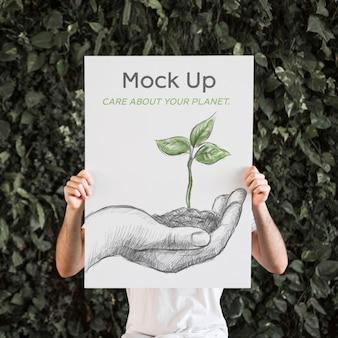 Uomo che presenta poster mockup di fronte a foglie