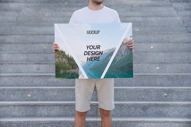 Uomo che presenta poster mockup di fronte a scale