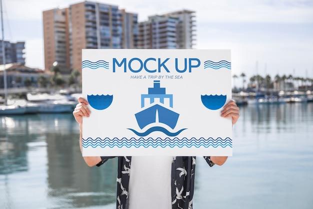 Uomo che presenta poster mockup di fronte all'acqua