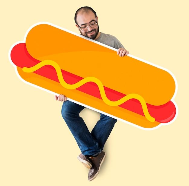 Uomo che tiene un grosso hot dog