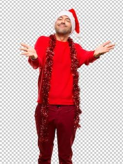 Uomo con abiti rossi che festeggiano le vacanze di natale che presentano e invitano a venire con la mano