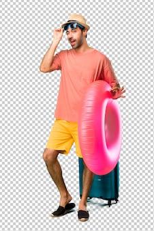 Uomo con cappello e occhiali da sole per le sue vacanze estive che mostrano un segno ok con le dita mentre strizza l'occhio