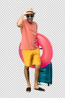 Uomo con cappello e occhiali da sole per le sue vacanze estive guardando lontano con la mano per guardare qualcosa