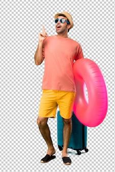 Uomo con cappello e occhiali da sole per le sue vacanze estive in piedi e pensando un'idea che punta il dito verso l'alto