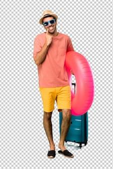 Uomo con cappello e occhiali da sole per le sue vacanze estive sorridendo con un'espressione felice e piacevole mentre punta la bocca e il viso con le dita
