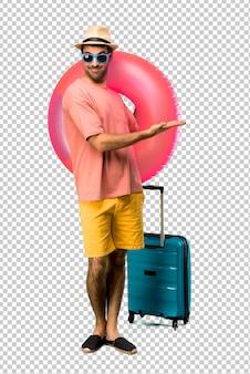 Uomo con cappello e occhiali da sole sulle sue vacanze estive che presentano un prodotto o un'idea mentre guardano sorridente verso