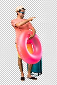 Uomo con cappello e occhiali da sole sulle sue vacanze estive che punta il dito verso il lato e presenta un prodotto in posizione laterale