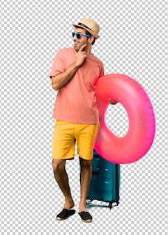 Uomo con cappello e occhiali da sole sulle sue vacanze estive in piedi e guardando di lato con la mano sul mento