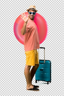 Uomo con cappello e occhiali da sole sulle sue vacanze estive salutando con la mano con espressione felice