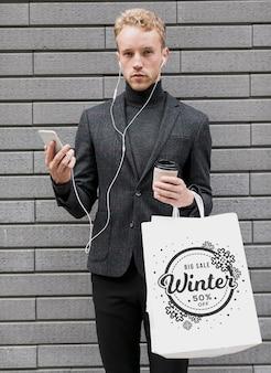 Uomo con i sacchetti della spesa e la tenuta del cellulare