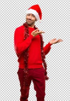 Uomo con i vestiti rossi che celebra le feste di natale che estendono le mani al lato