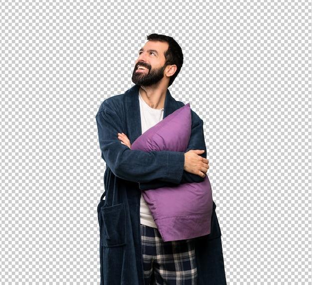 Uomo con la barba in pigiama che osserva in su mentre sorridendo