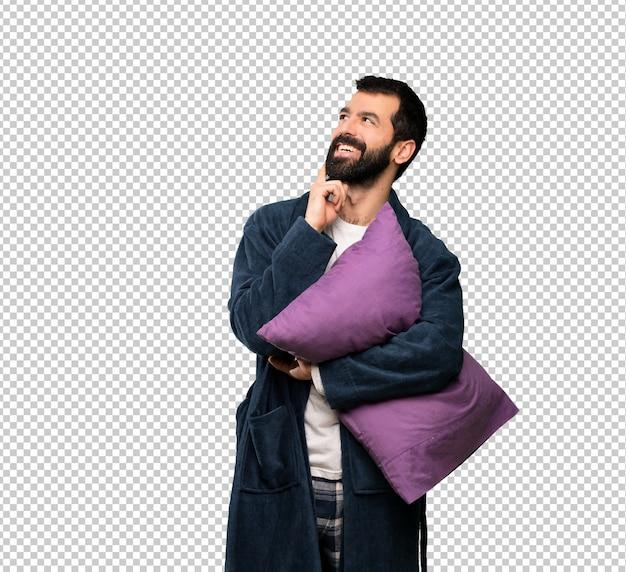 Uomo con la barba in pigiama pensando un'idea mentre alzando lo sguardo