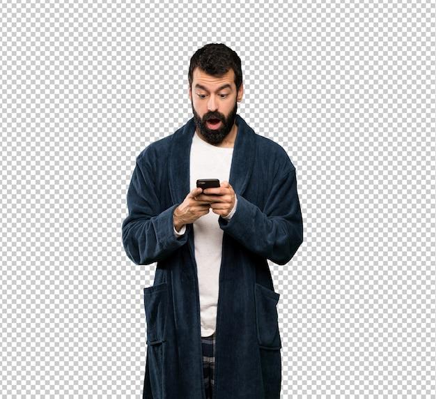 Uomo con la barba in pigiama sorpreso e inviando un messaggio