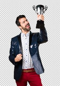 Uomo con la giacca che tiene un trofeo