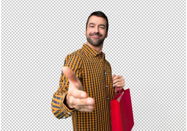 Uomo con le borse della spesa che stringono le mani per la chiusura di un buon affare
