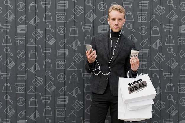 Uomo con le mani piene di borse per la spesa