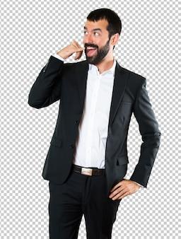 Uomo d'affari bello che fa gesto del telefono