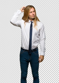 Uomo d'affari biondo con capelli lunghi che hanno dubbi mentre graffiano la testa