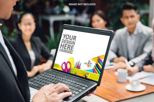 Uomo d'affari che fa presentazione con il modello dello schermo del computer portatile