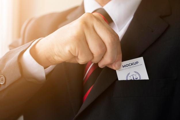Uomo d'affari che mette il modello di biglietto da visita in tasca