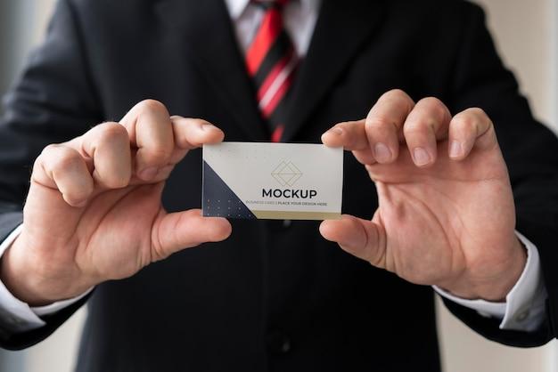Uomo d'affari del primo piano che tiene il modello del biglietto da visita con entrambe le mani