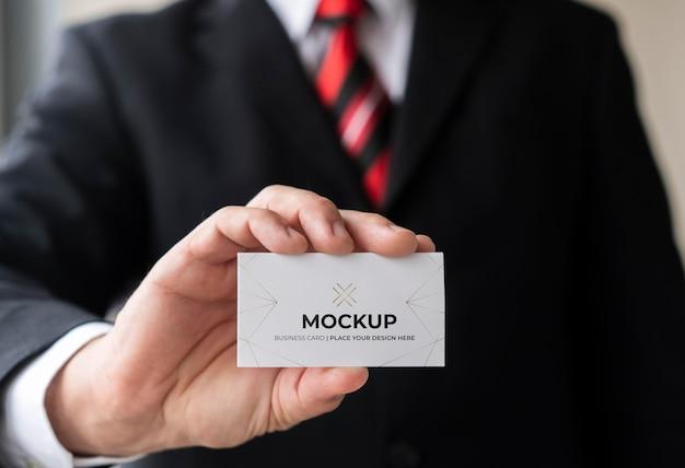 Uomo d'affari del primo piano che tiene il modello del biglietto da visita con una mano