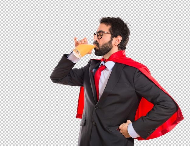 Uomo d'affari hipster vestito come un supereroe che beve succo d'arancia