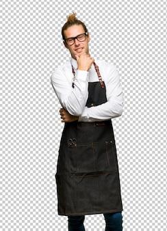 Uomo del barbiere in un grembiule con gli occhiali e sorridente