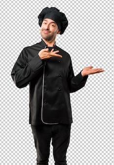 Uomo del cuoco unico in uniforme nera che estende le mani al lato e che sorride per presentarsi
