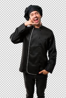 Uomo del cuoco unico in uniforme nera che fa gesto del telefono e che parla con qualcuno. chiamami segno