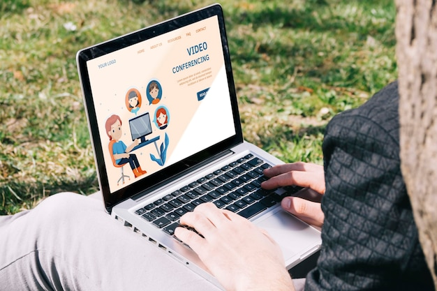 Uomo del primo piano con il computer portatile all'aperto