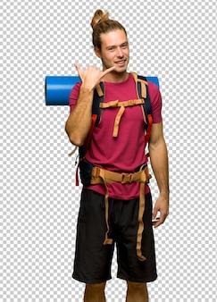 Uomo della viandante con lo zaino in spalla della montagna che fa gesto del telefono. chiamami segno