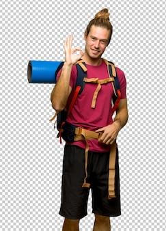 Uomo della viandante con lo zaino in spalla della montagna che mostra un segno giusto con le dita