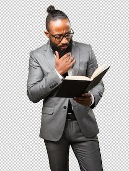 Uomo di colore che tiene un libro